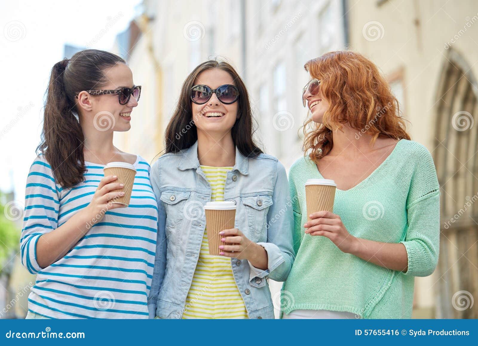 Szczęśliwe młode kobiety pije kawę na miasto ulicie