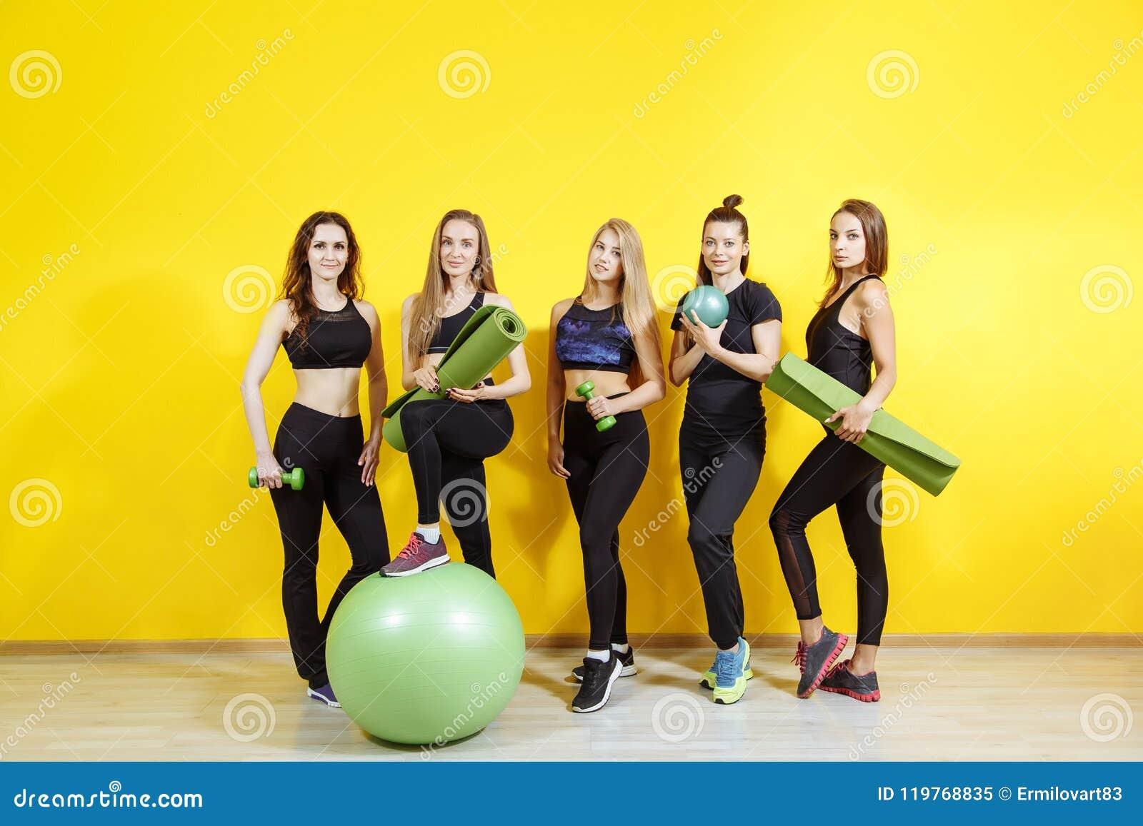 Szczęśliwe młode kobiety stoi wpólnie i ono uśmiecha się po ćwiczyć Grupa żeńscy przyjaciele relaksuje po treningu
