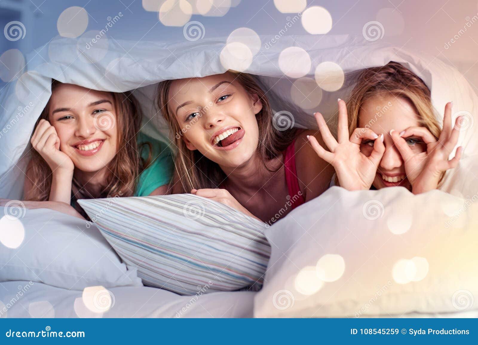 Szczęśliwe młode kobiety w łóżko piżamy przyjęciu w domu