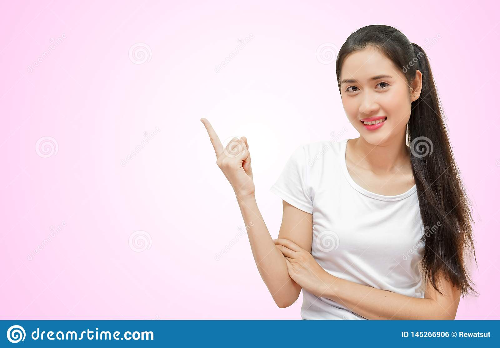 Szczęśliwe młode piękne kobiety w t-sirt prawej ręce wskazywali pozycję odizolowywającą na różowym miękkim tle