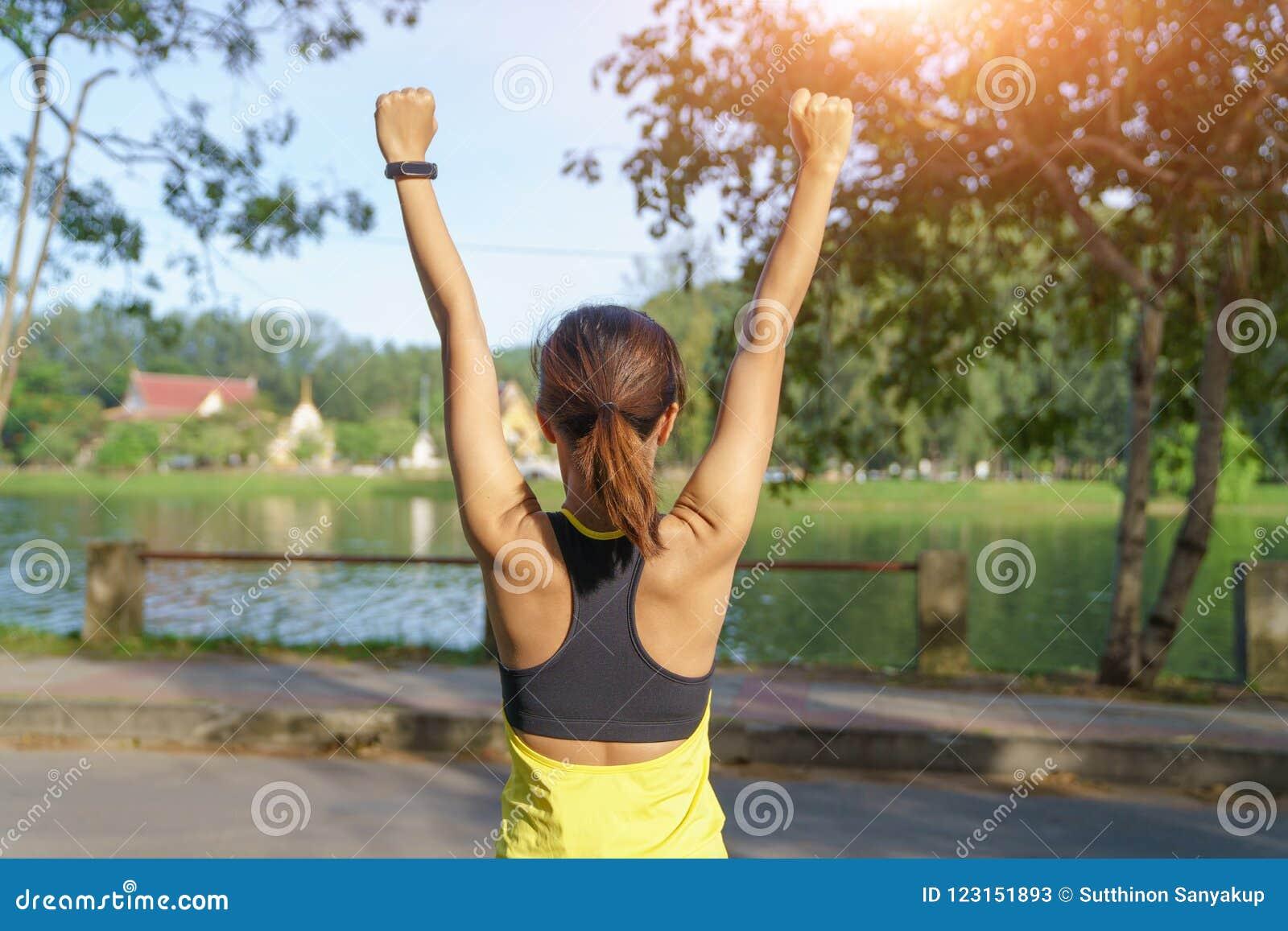 Szczęśliwe pomyślne sportsmenki dźwigania ręki niebo na złotym tylnym oświetleniowym zmierzchu lecie Sprawności fizycznej atleta