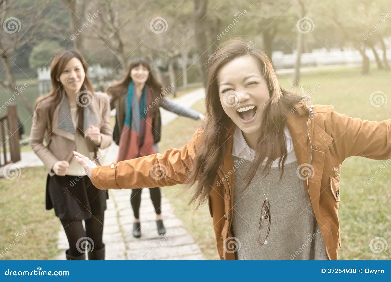 Szczęśliwe uśmiechnięte Azjatyckie kobiety bawić się w parku