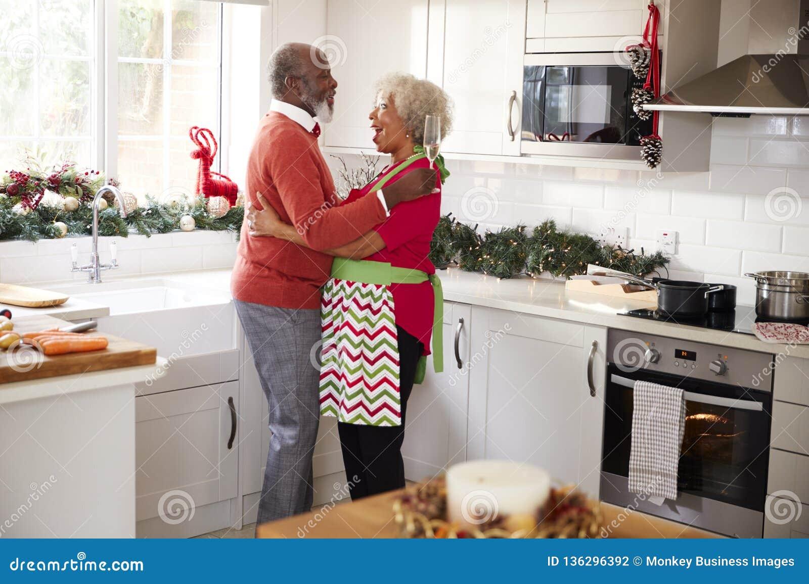Szczęśliwego dojrzałego czarnego pary mienia szampańscy szkła śmia się i obejmuje w kuchni, podczas gdy przygotowywający posiłek