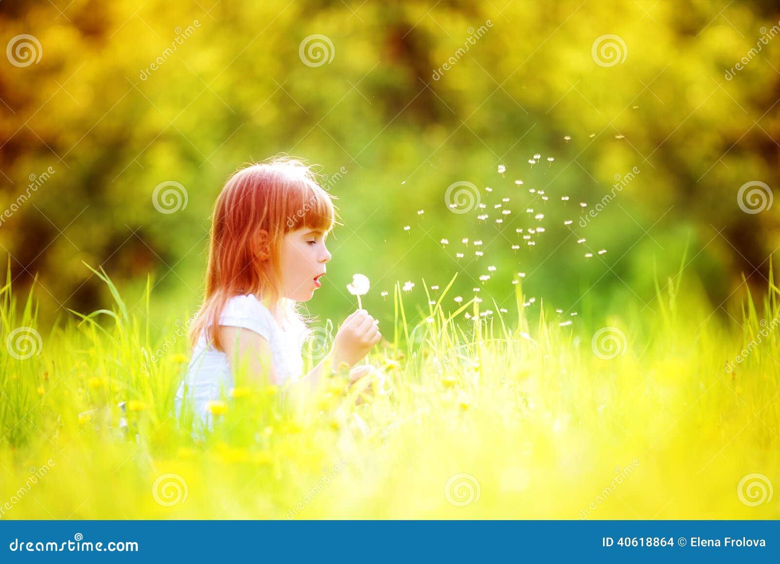 Szczęśliwego dziecka podmuchowy dandelion outdoors w wiosna parku