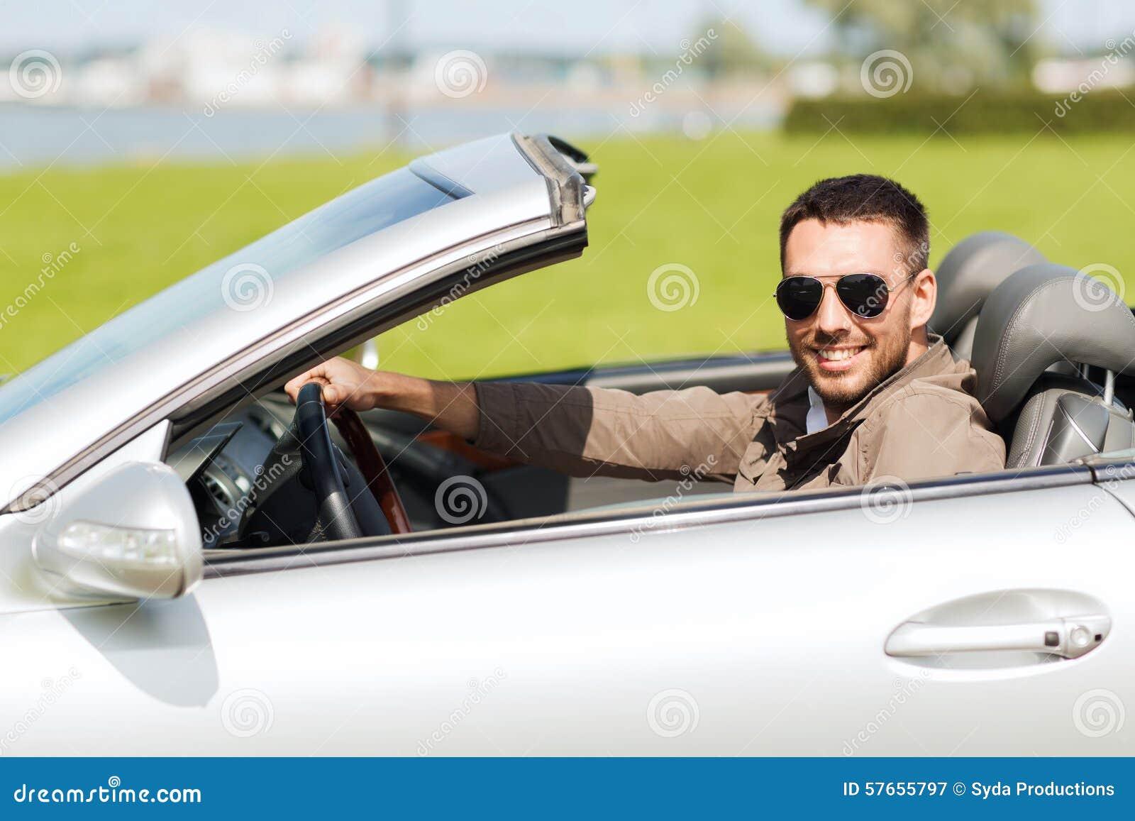 Szczęśliwego mężczyzna kabrioletu napędowy samochód outdoors