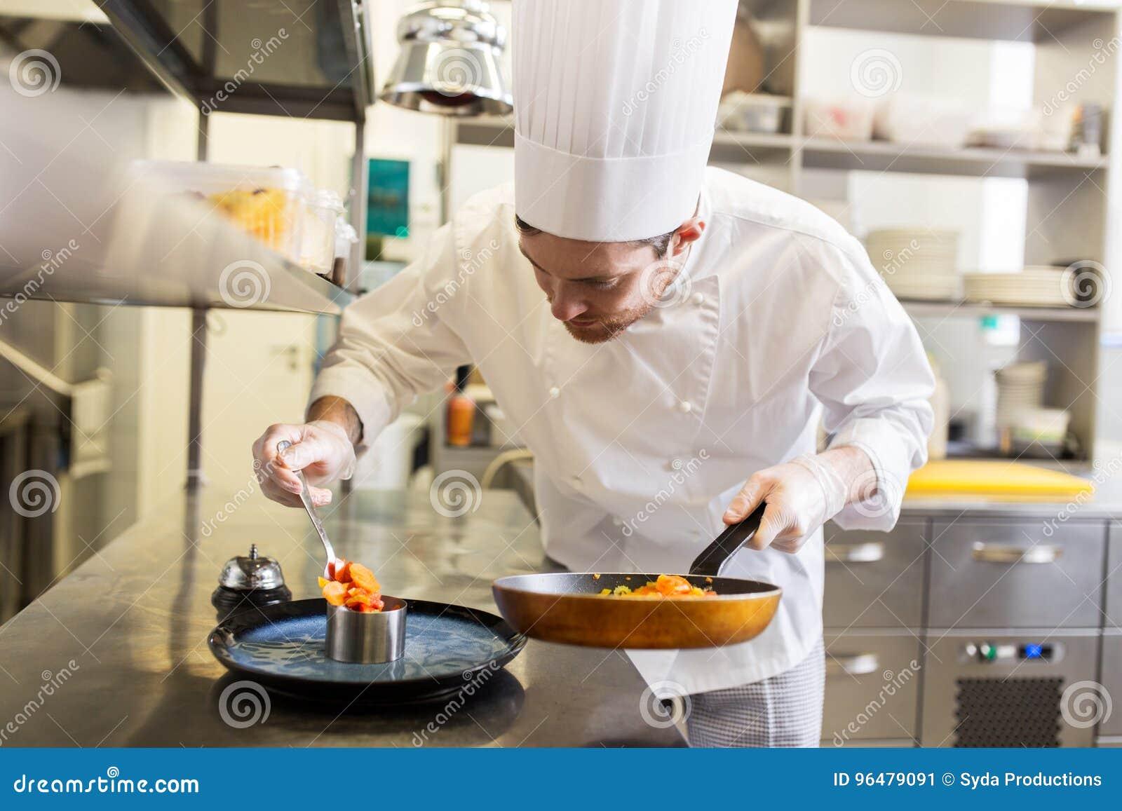 Szczęśliwego męskiego szefa kuchni kulinarny jedzenie przy restauracyjną kuchnią