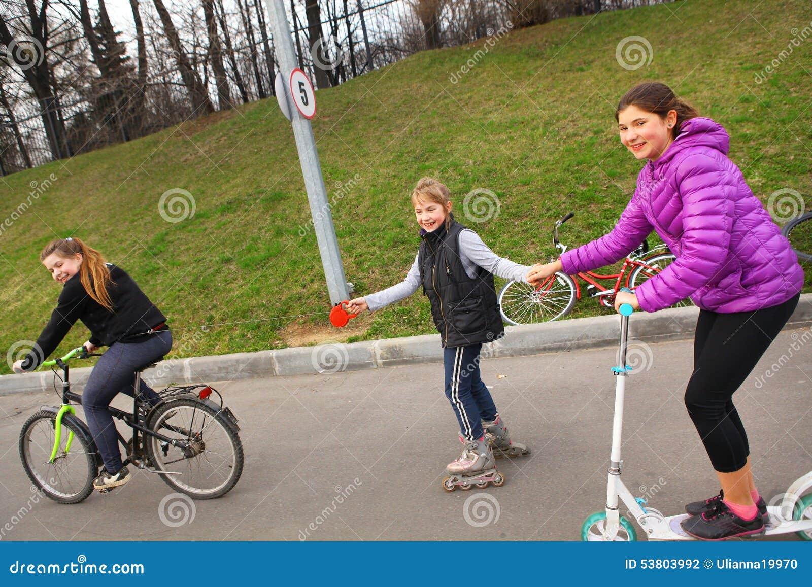 Szczęśliwej dziewczyna przyjaciela przejażdżki rolkowe łyżwy hulajnoga i bicykl na holowniczym