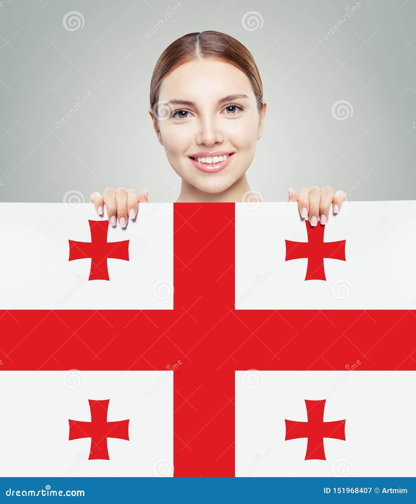 Szczęśliwej dziewczyny uśmiechnięty uczeń z Gruzja flagi tłem