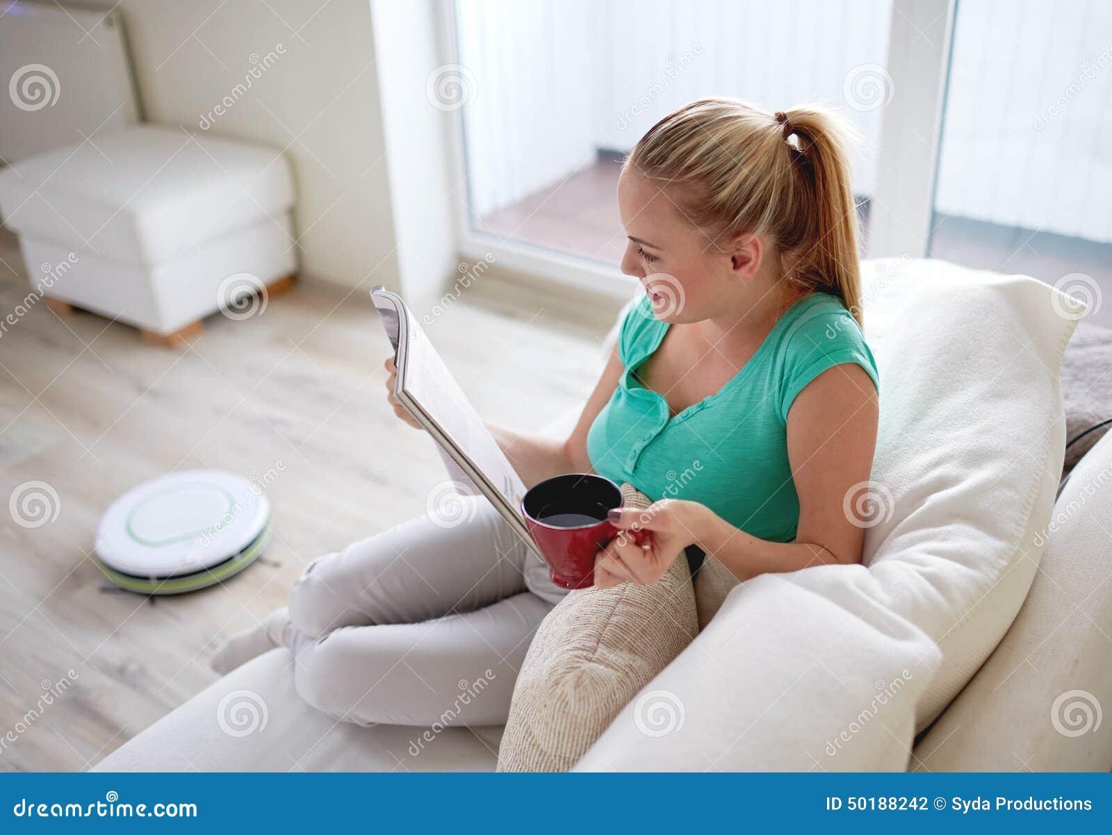 Szczęśliwej kobiety czytelniczy magazyn z herbacianą filiżanką w domu