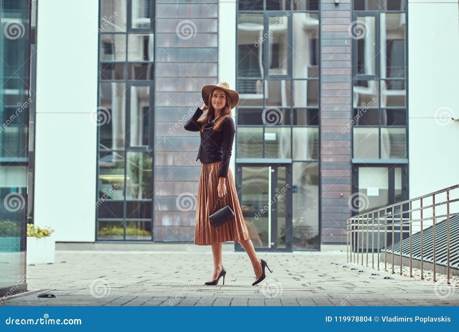Szczęśliwej mody elegancka kobieta jest ubranym czarną kurtkę, brown kapelusz i spódnica z torebką, trzymamy mocno odprowadzenie