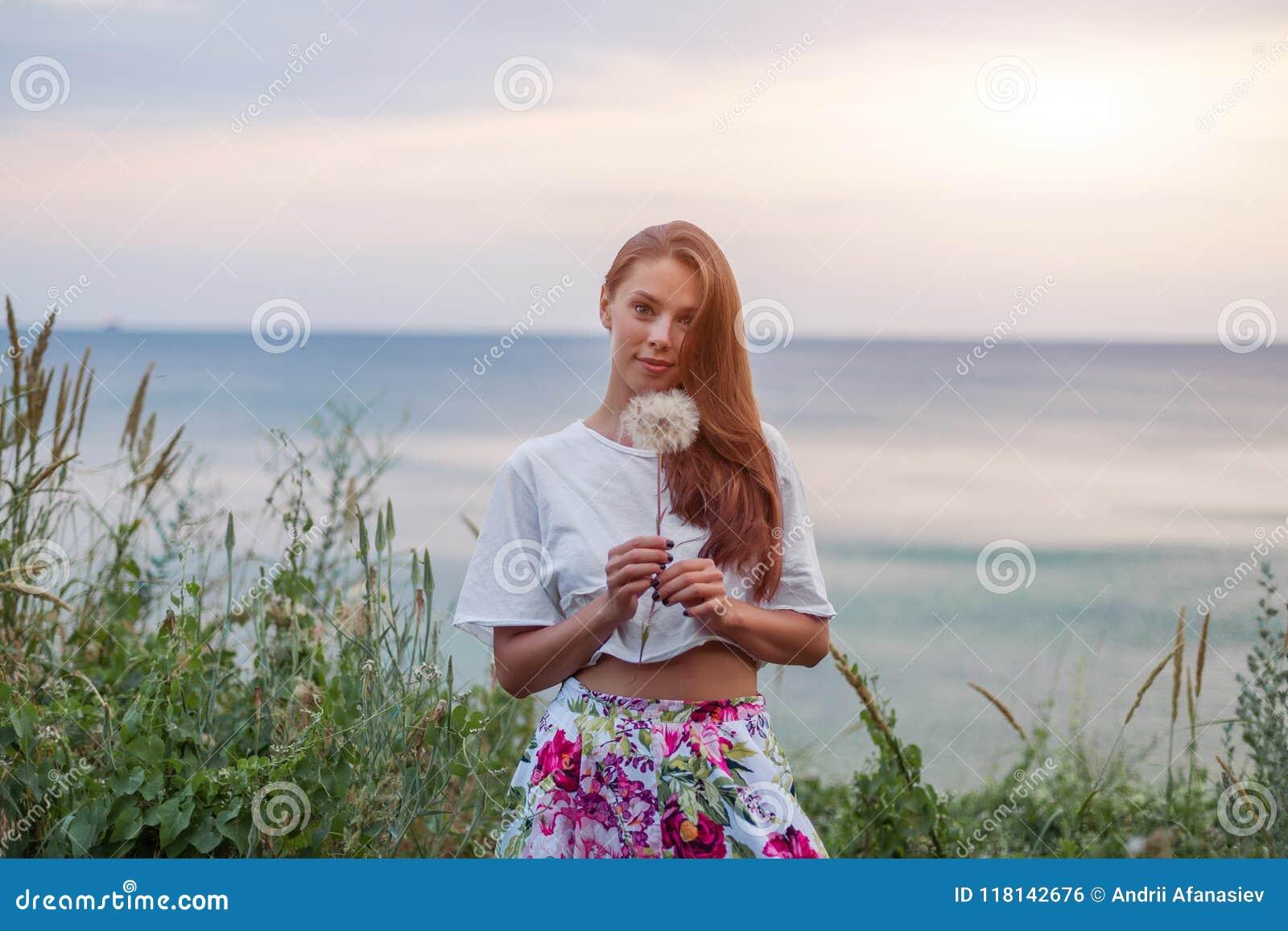 Szczęśliwej pięknej kobiety podmuchowy dandelion nad nieba i morza tłem, mieć zabawę i bawić się plenerowej, nastoletniej dziewcz