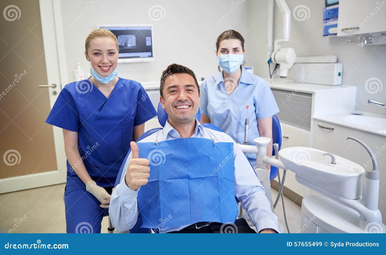 Szczęśliwi żeńscy dentyści z mężczyzna pacjentem przy kliniką