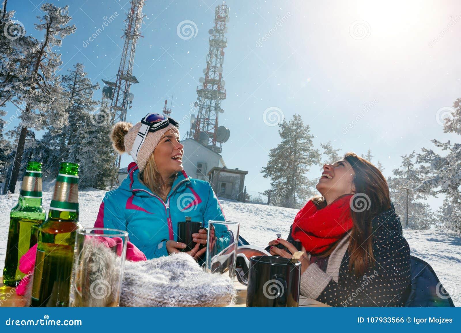 Szczęśliwi żeńscy przyjaciele cieszy się gorącego napój w kawiarni przy ośrodkiem narciarskim