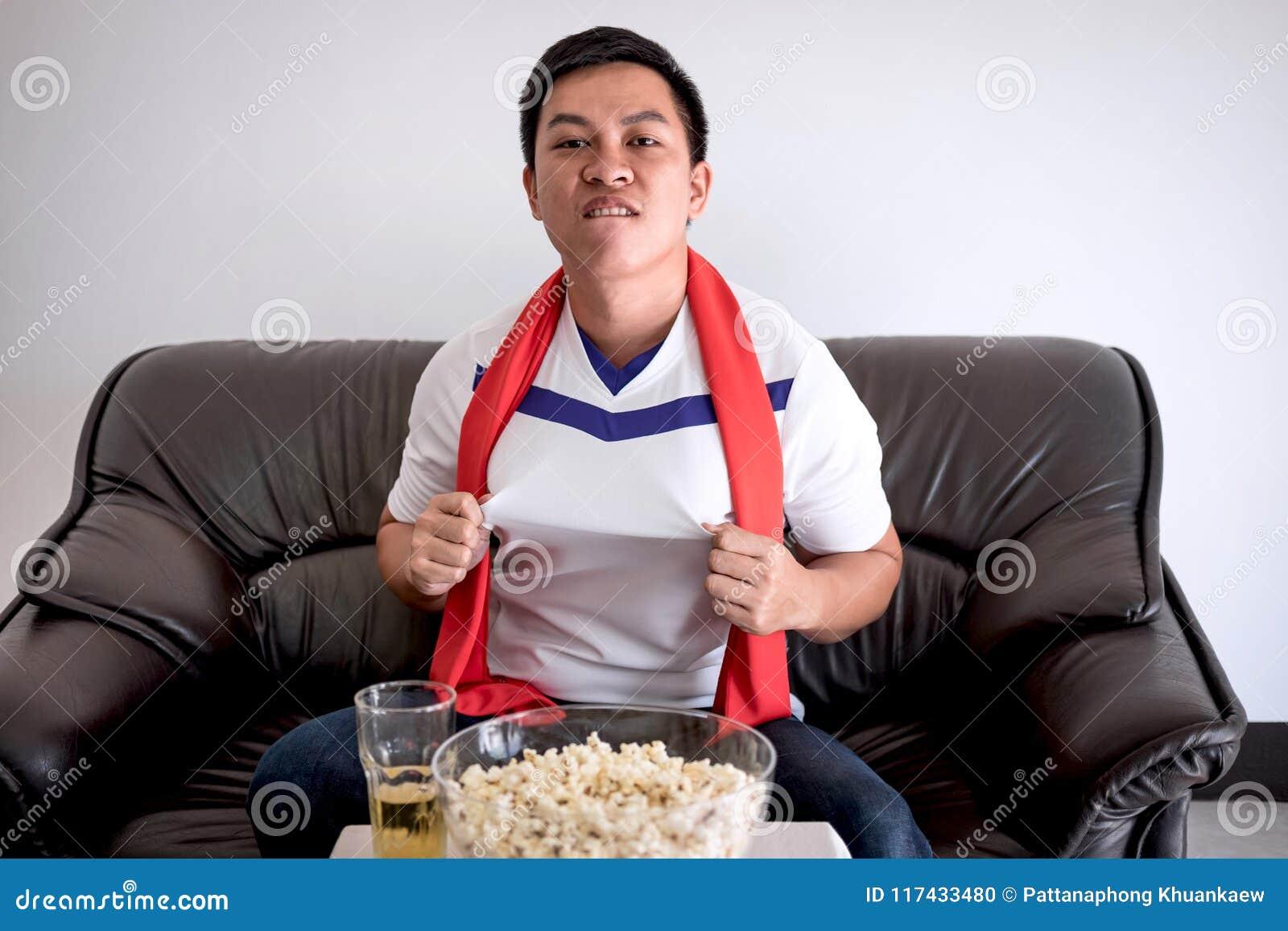 Szczęśliwi Azjatyccy mężczyzna ogląda mecz piłkarskiego na tv i rozweselać footbal