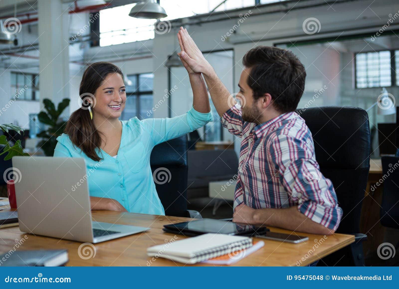 Szczęśliwi dyrektory wykonawczy daje wysokości pięć przy biurkiem