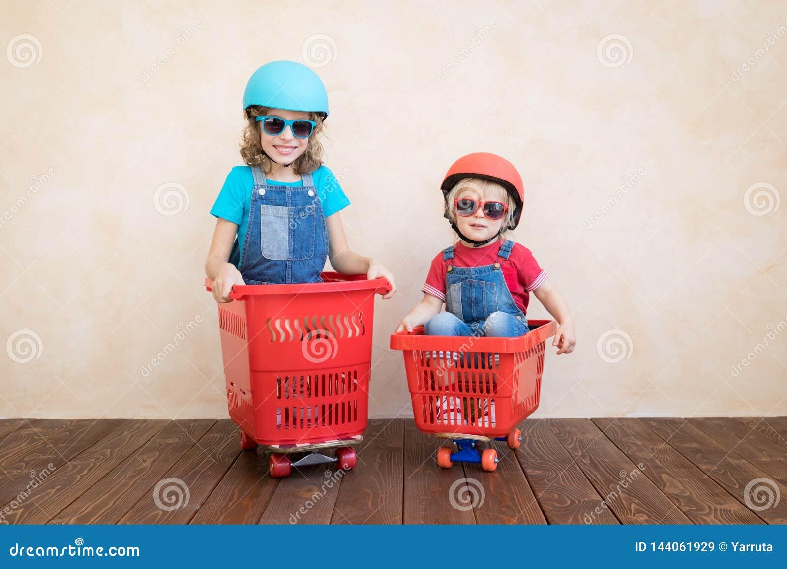 Szczęśliwi dzieci jedzie zabawkarskiego samochód w domu