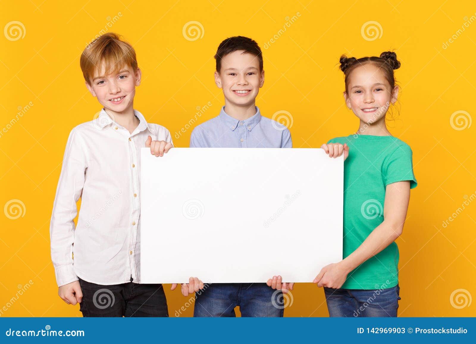 Szczęśliwi dzieci trzyma pustego sztandar dla reklamy