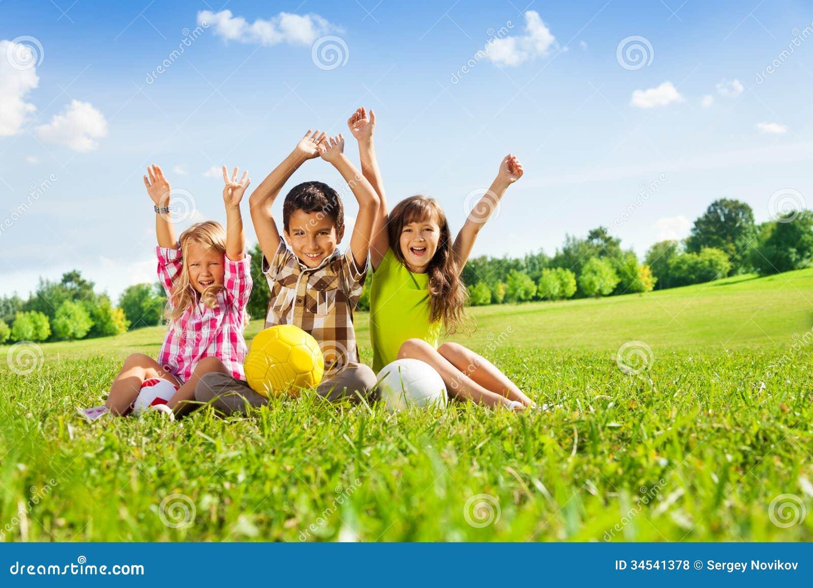 Szczęśliwi dzieciaki z piłkami i podnosić rękami