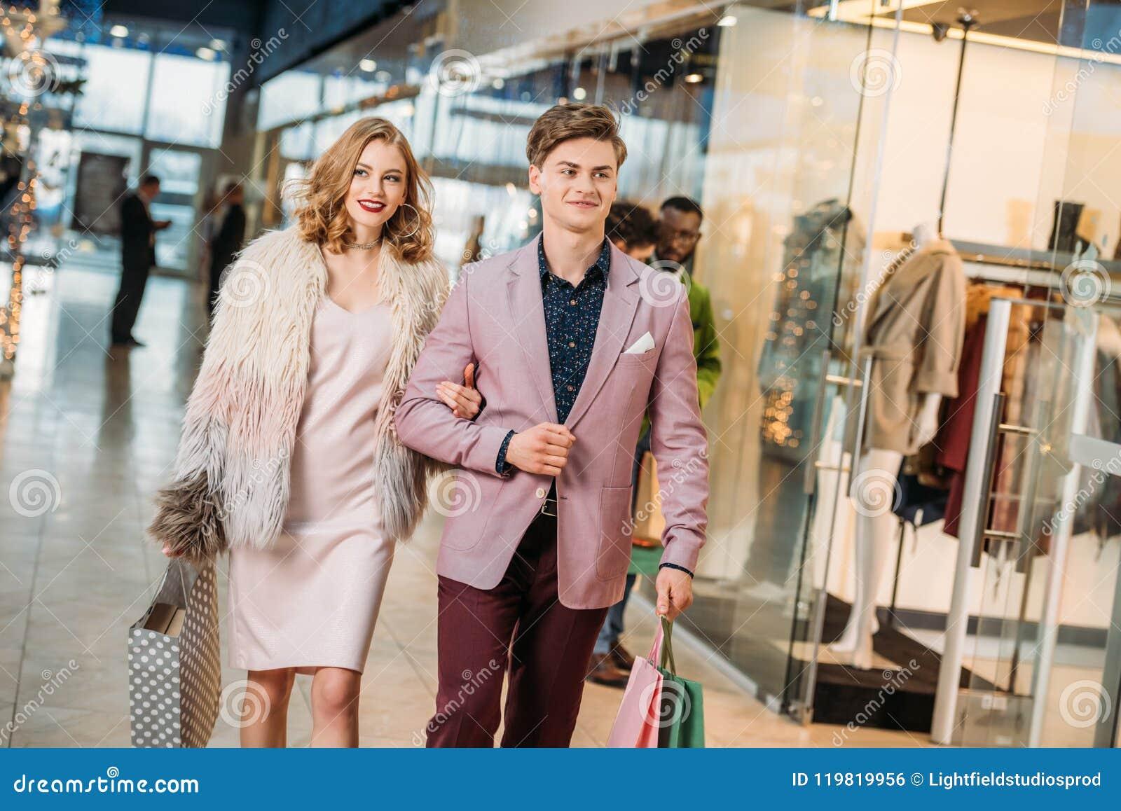 Szczęśliwi eleganccy potomstwa dobierają się z torba na zakupy chodzi wpólnie