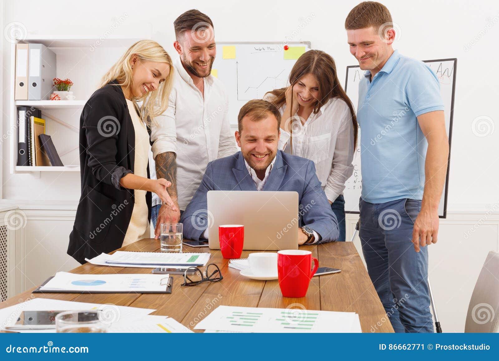 Szczęśliwi ludzie biznesu zespalają się wpólnie zabawę w biurze