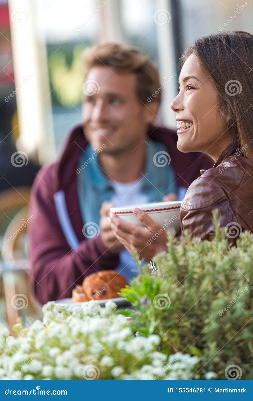 Szczęśliwi ludzie je śniadanio-lunch przy kawiarnią Potomstwo pary modnisie pije kawę przy restauracja stołem na zewnątrz chodnic