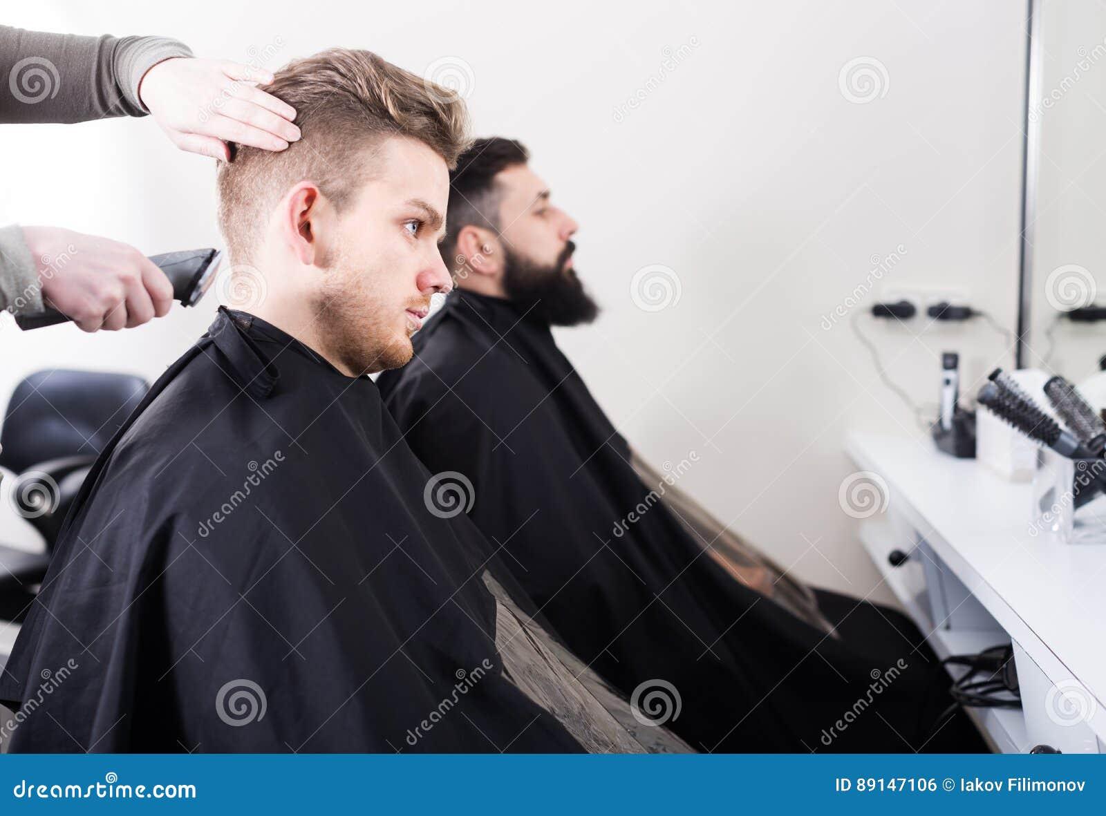 Szczęśliwi mężczyzna ma ich włosy ciącego fryzjerami