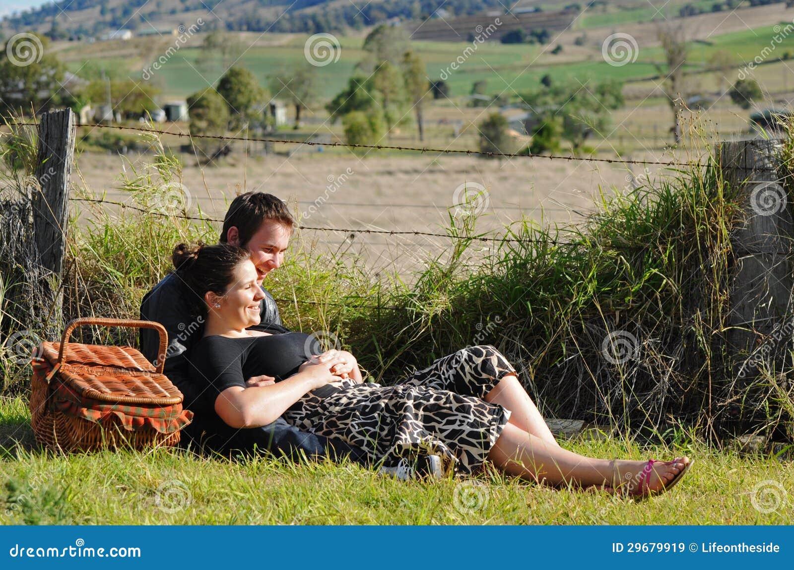 Szczęśliwi młodzi kochankowie roześmiani & one uśmiechają się outdoors