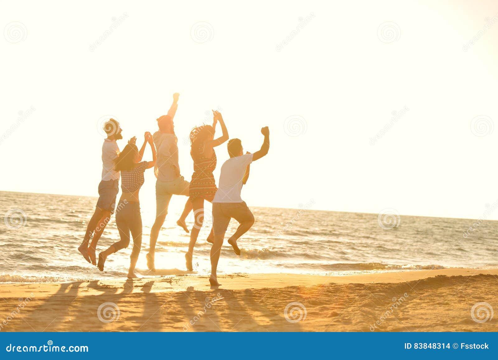 Szczęśliwi młodzi ludzie grup zabawy białego doskakiwanie na beacz i bieg przy zmierzchu czasem