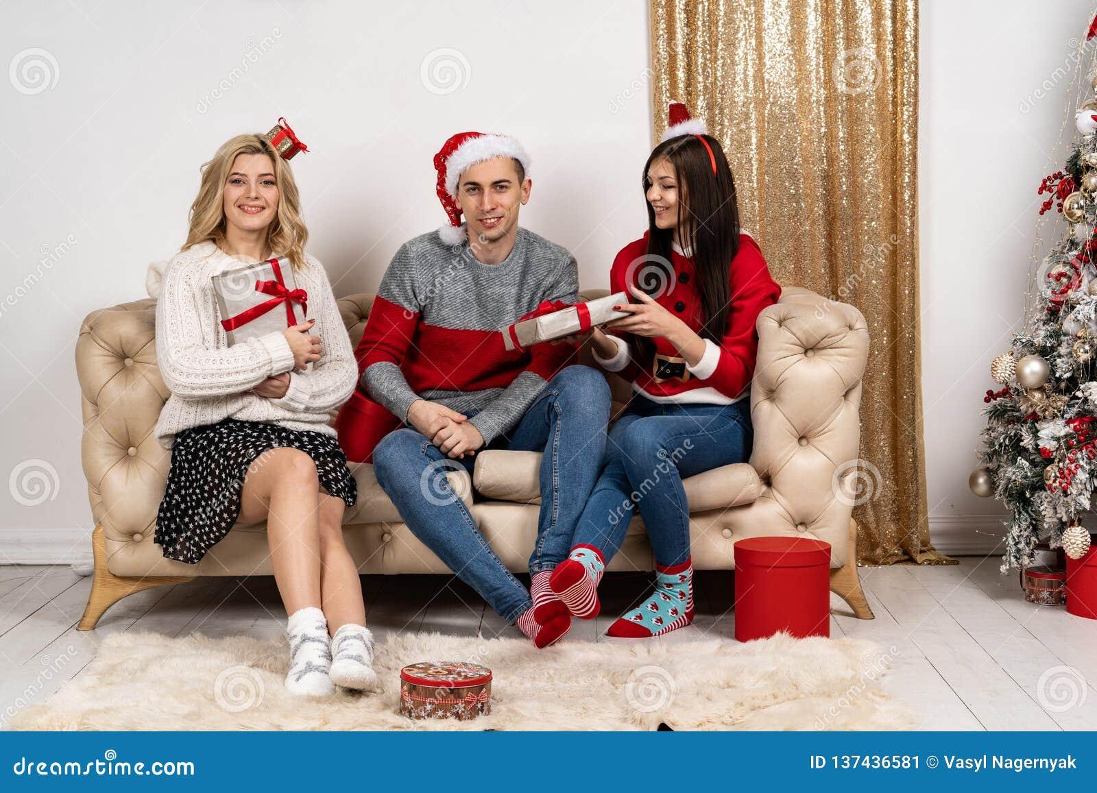 Szczęśliwi młodzi ludzie siedzi na kanapie w pulowerach i Santa kapeluszach