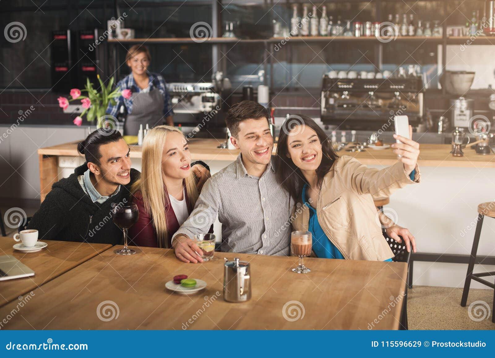 Szczęśliwi młodzi przyjaciele pije kawę przy kawiarnią