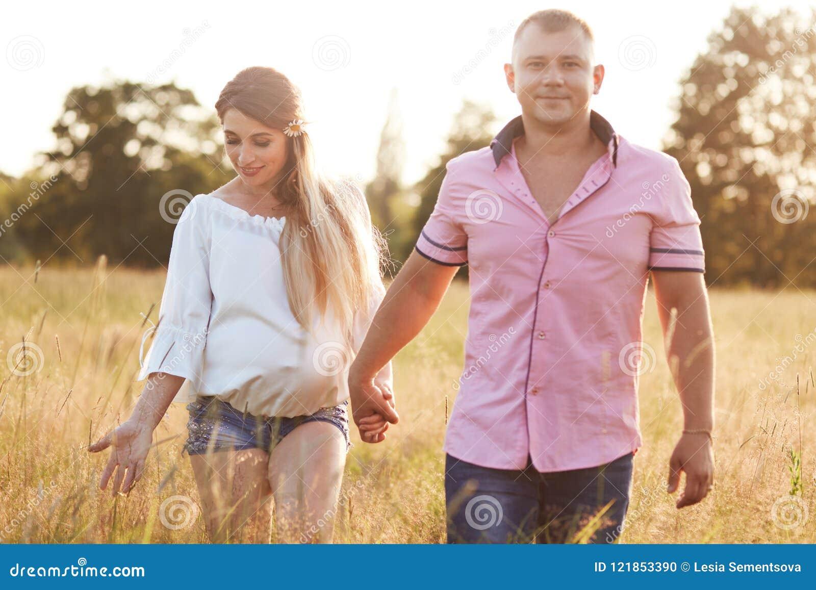 Szczęśliwi młodzi przyszłościowi rodzice przespacerowanie przez zieloną łąkę, trzymają ręki, cieszą się spokojną atmosferę, szczę