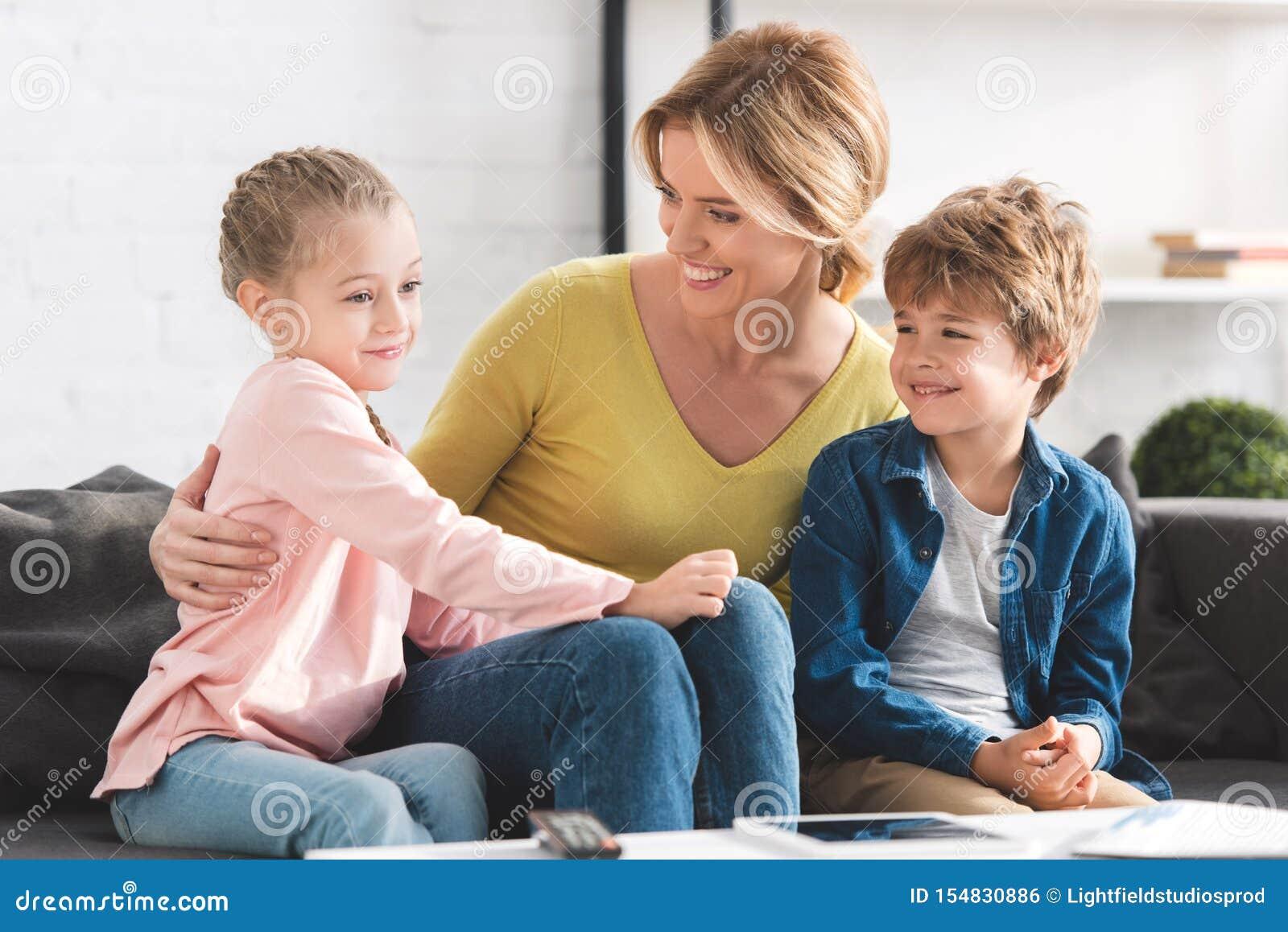 Szczęśliwi macierzyści patrzeje uroczy uśmiechnięci dzieci siedzi wpólnie