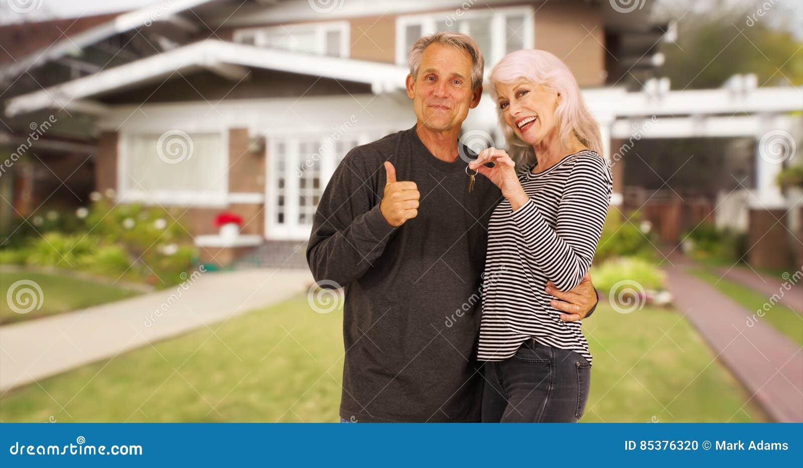 Szczęśliwi nowi starsi właściciele domu ono uśmiecha się przy kamerą