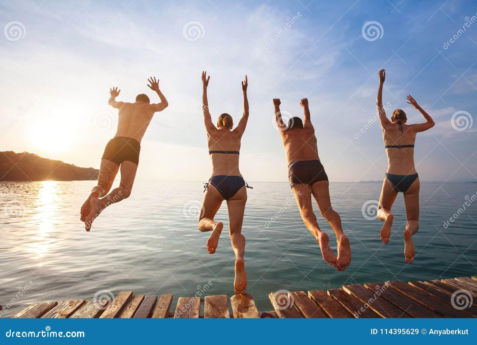 Szczęśliwi plażowi wakacje, grupa przyjaciele skacze woda