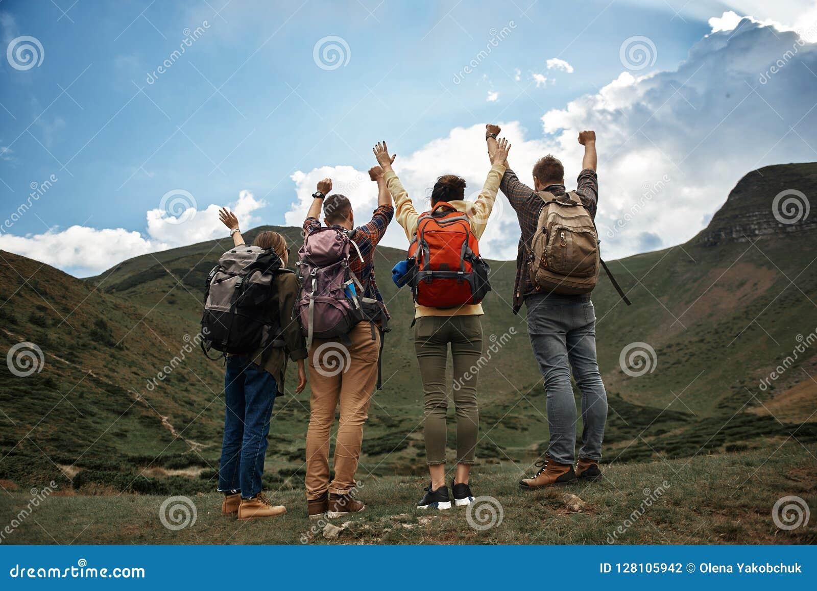Szczęśliwi podróżnicy stawia ręki up po dosięgać wierzchołek
