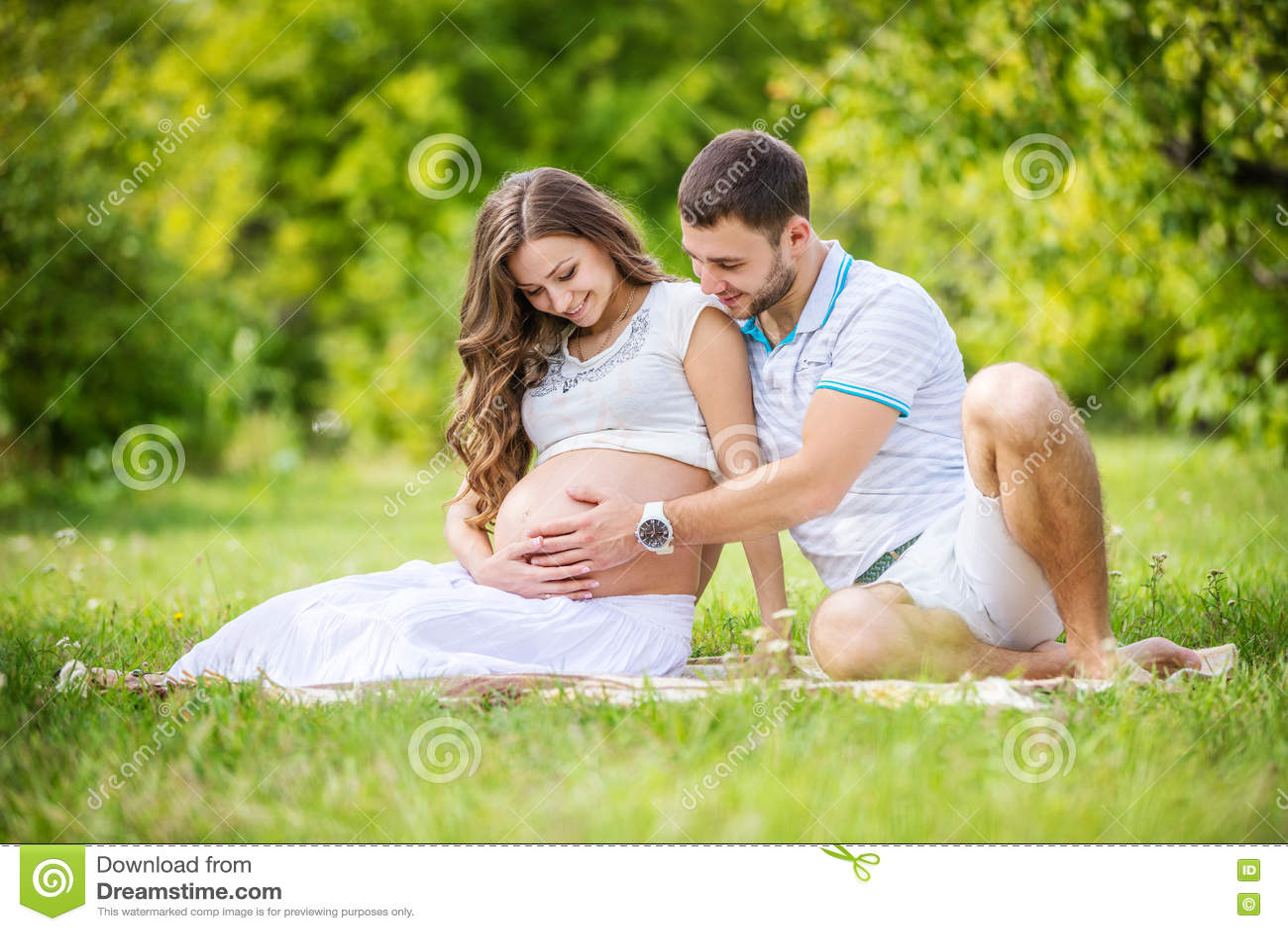 Szczęśliwi potomstwa dobierają się oczekiwać dziecka, kobieta w ciąży z męża wzruszającym brzuchem