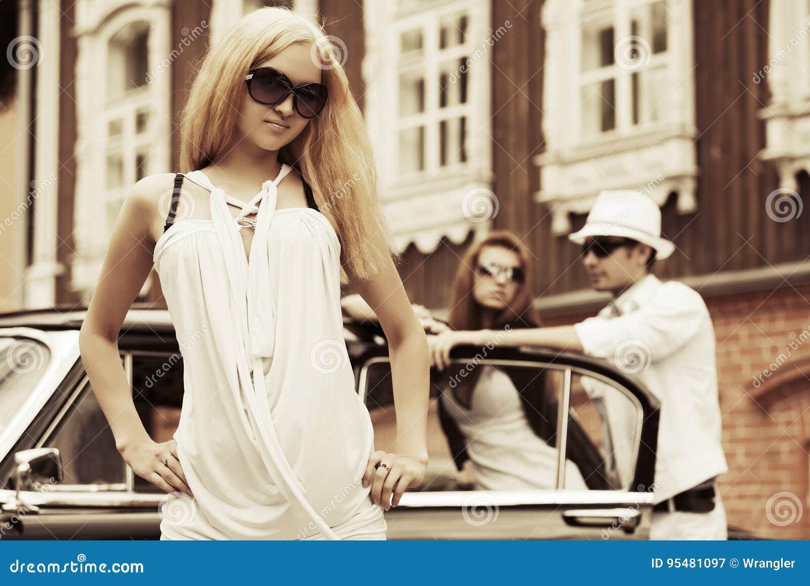 Szczęśliwi potomstwa fasonują blond kobiety w biel sukni obok rocznika samochodu