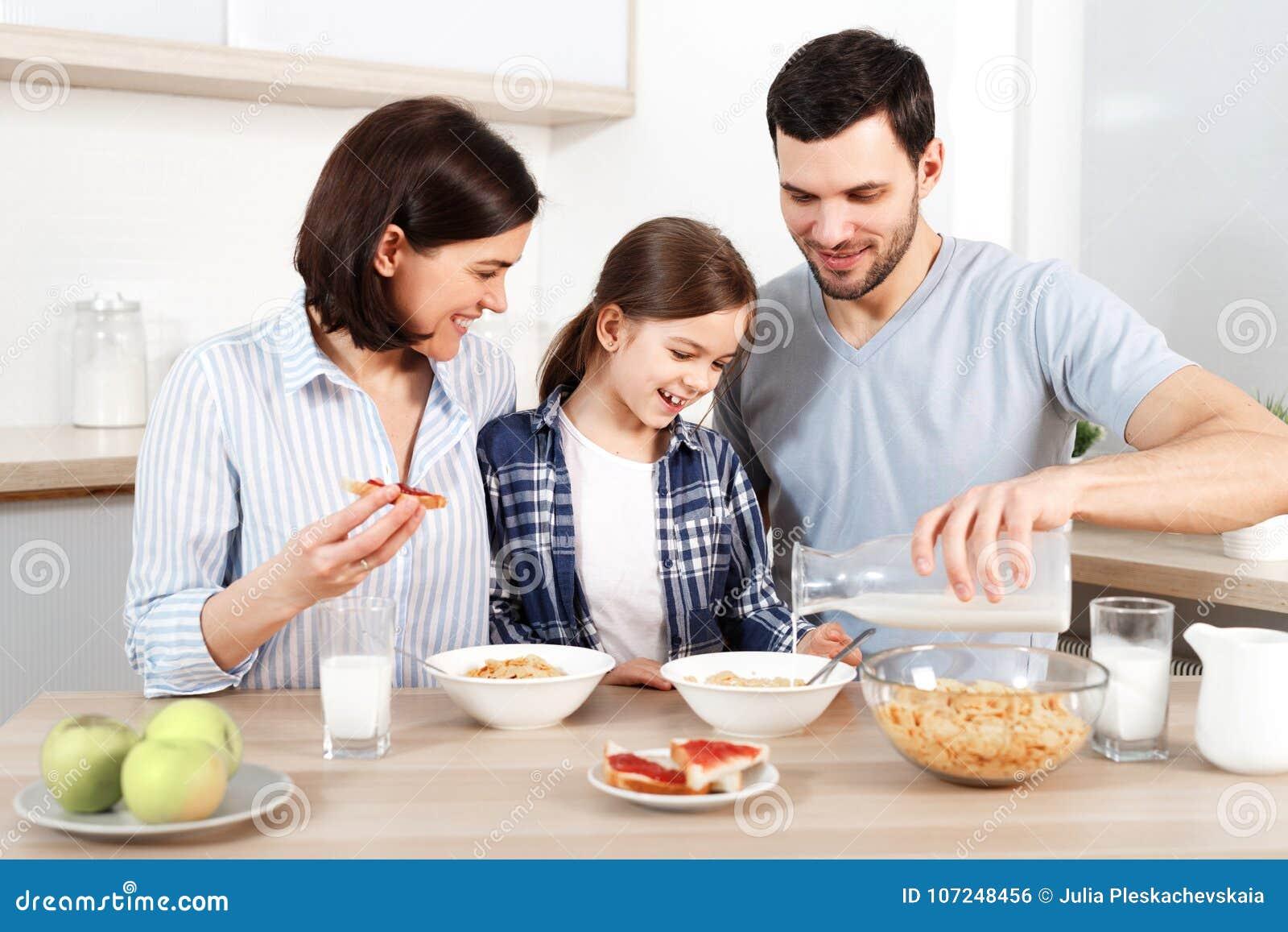 Szczęśliwi potomstwa wychowywają i ich urocza córka siedzi wpólnie przy kuchennym stołem, je płatki, zdrowego śniadanie, cieszy s