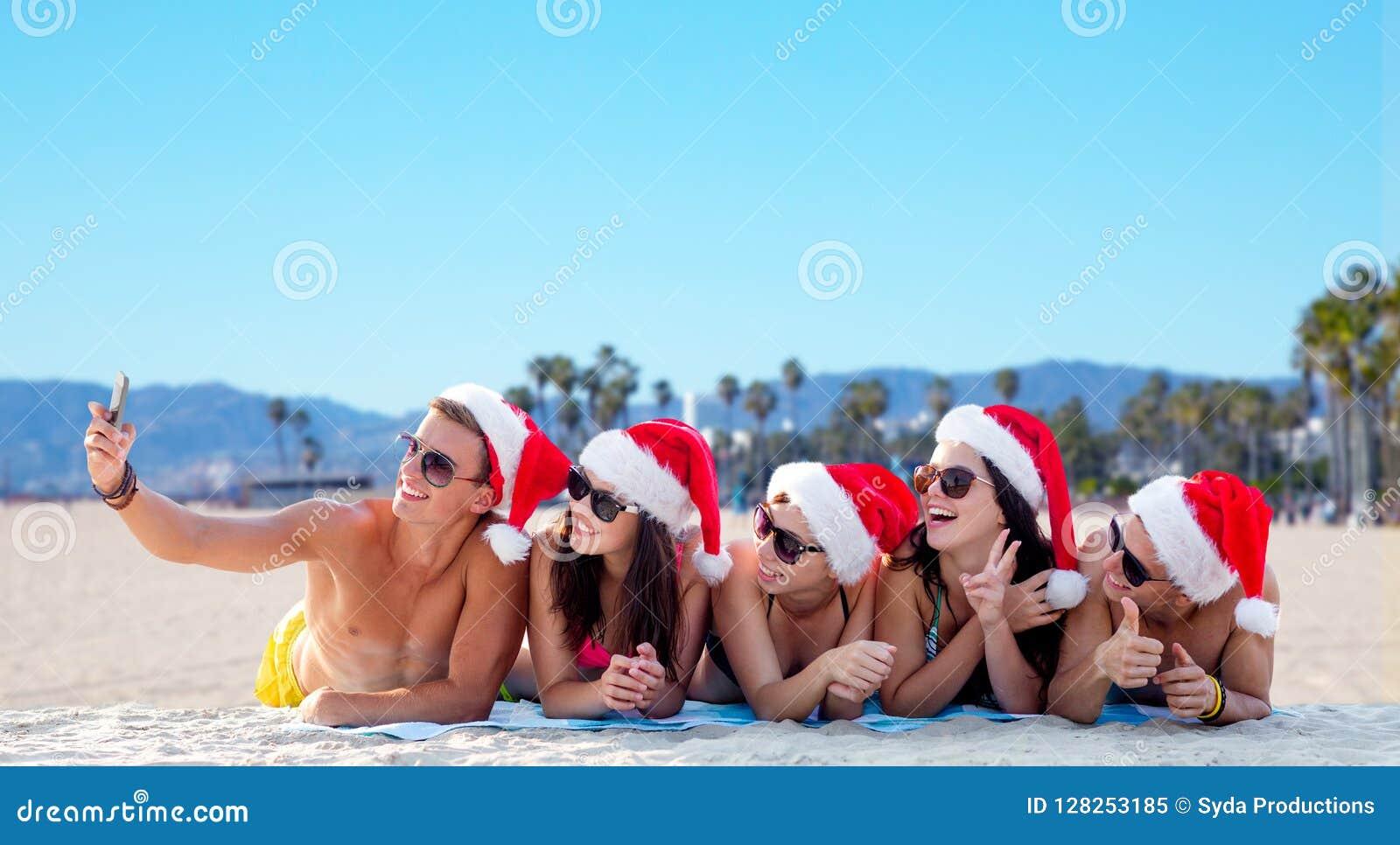 Szczęśliwi przyjaciele bierze selfie na plaży na bożych narodzeniach