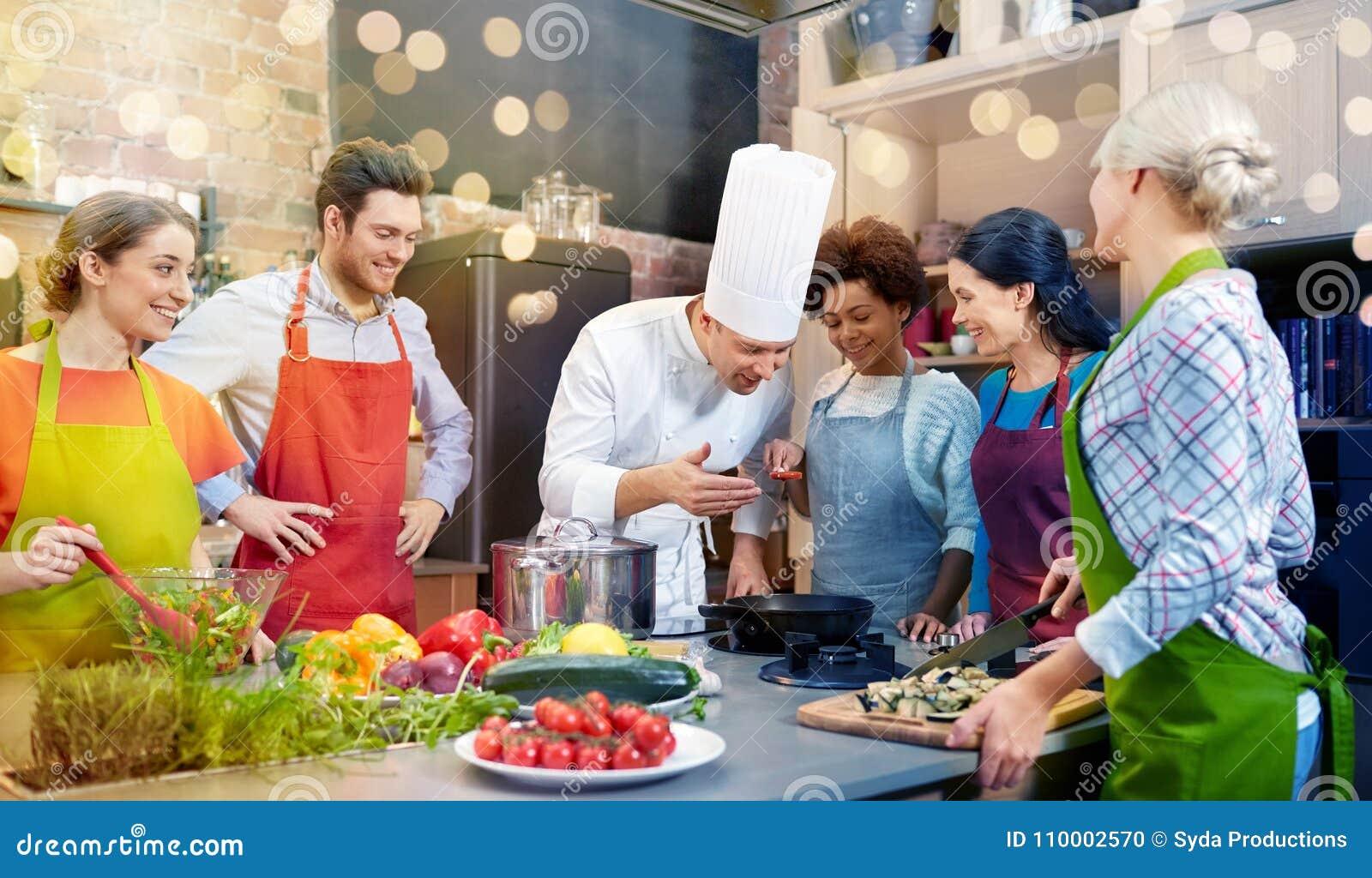 Szczęśliwi przyjaciele i szefa kuchni kucbarski kucharstwo w kuchni