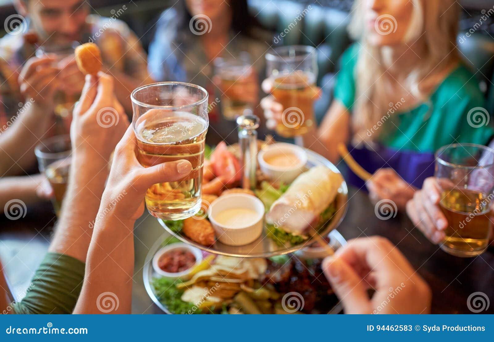 Szczęśliwi przyjaciele je i pije przy barem lub pubem