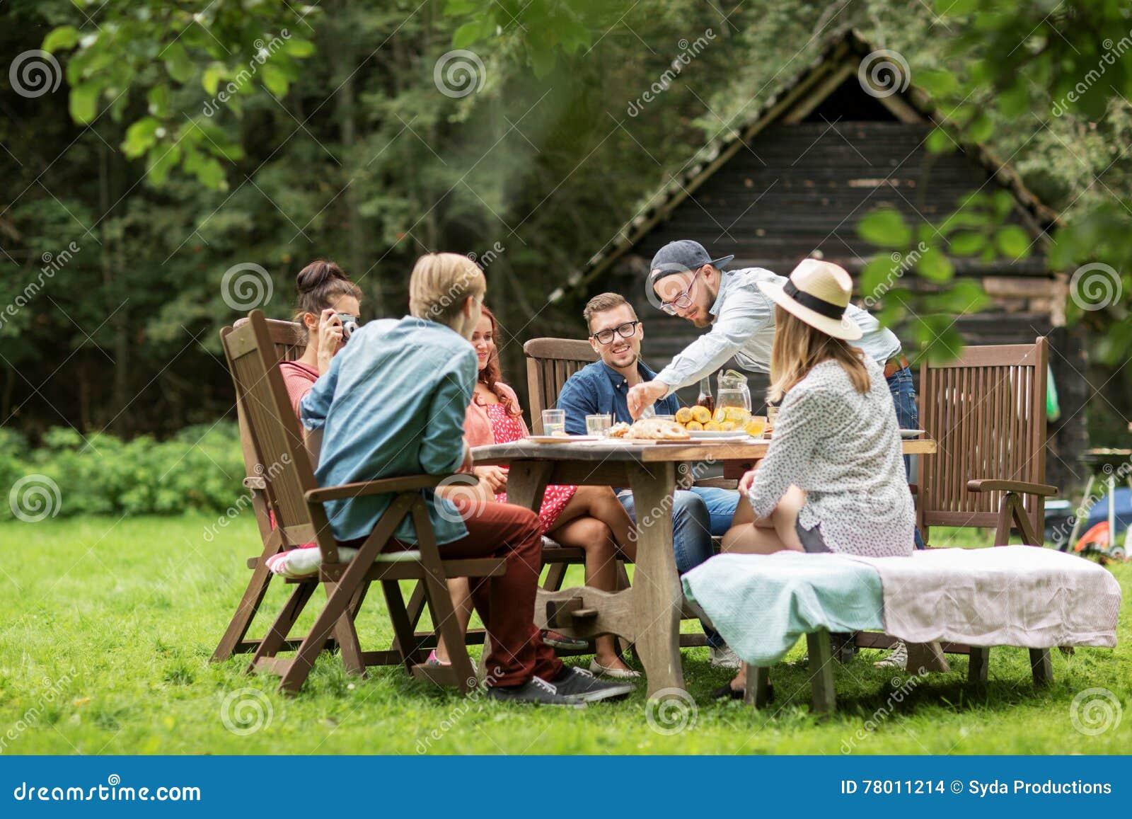 Szczęśliwi przyjaciele ma gościa restauracji przy lata ogrodowym przyjęciem