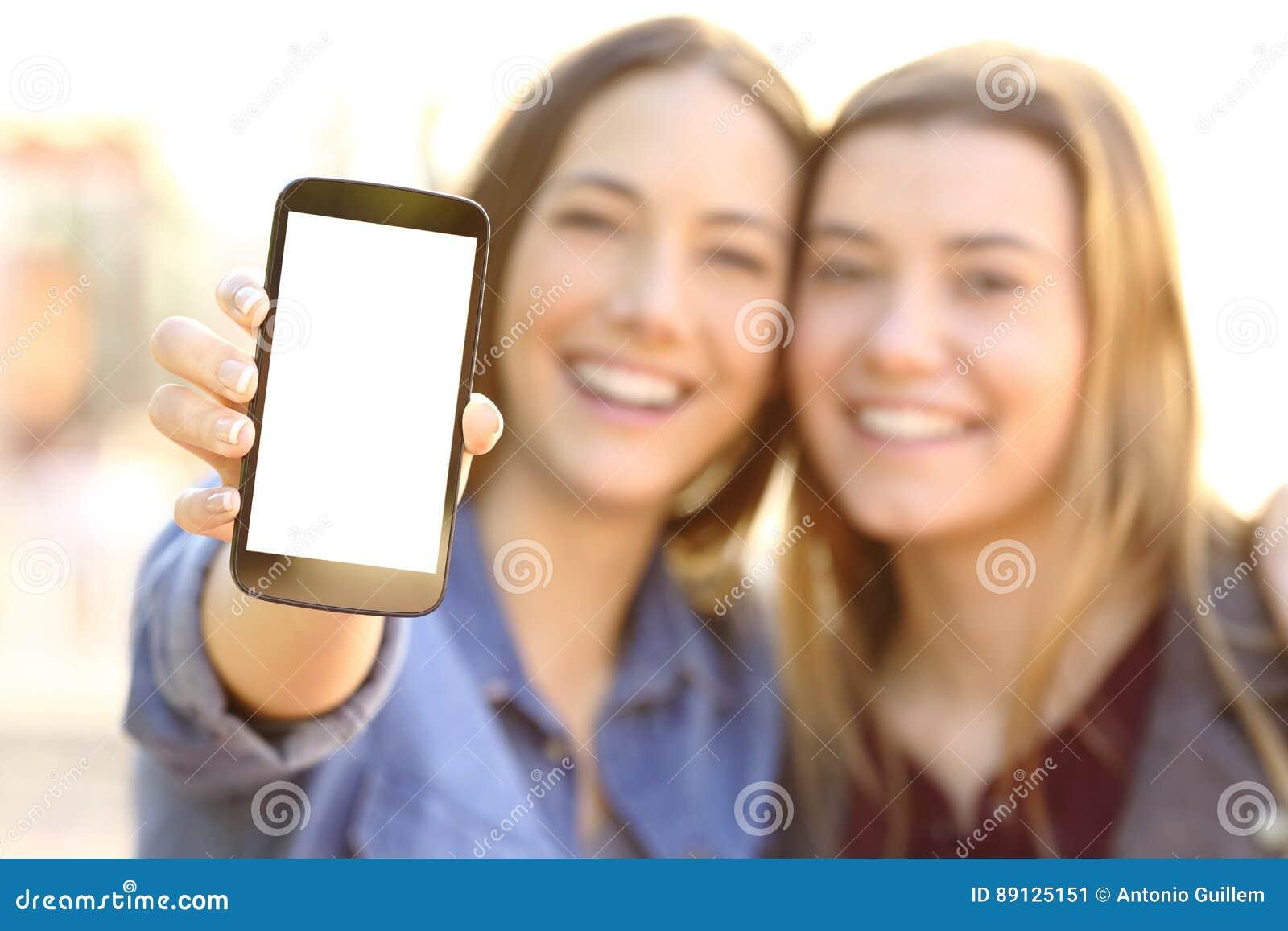 Szczęśliwi przyjaciele pokazuje pustego telefonu ekran