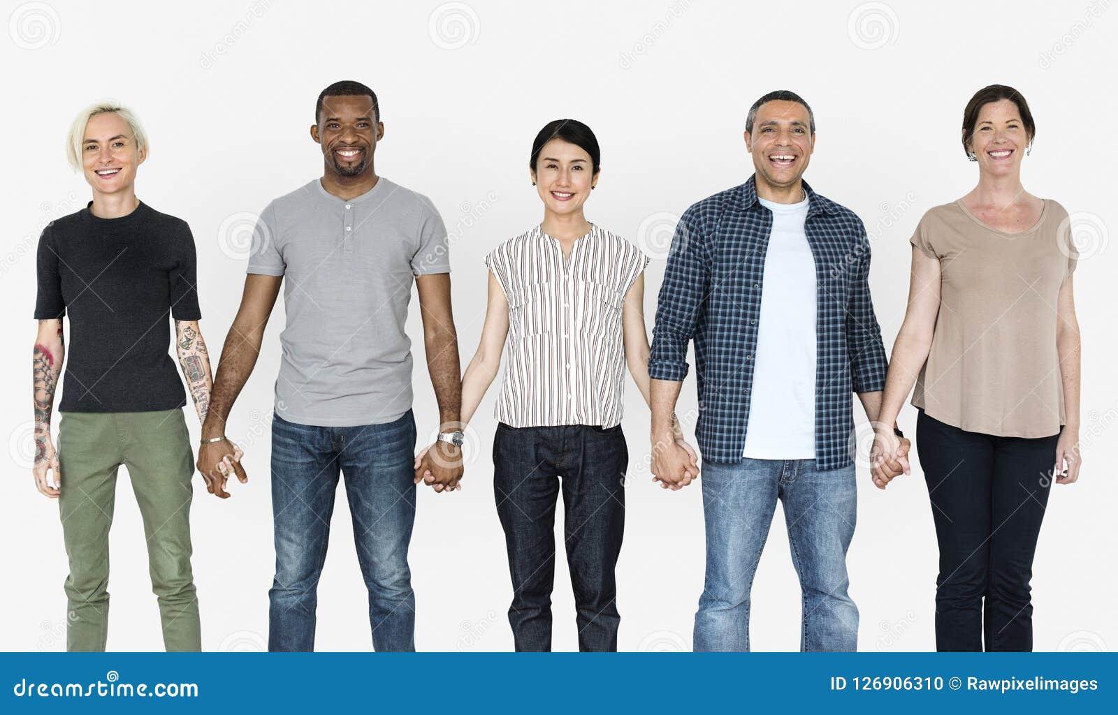 Szczęśliwi różnorodni ludzie trzyma ręki wpólnie