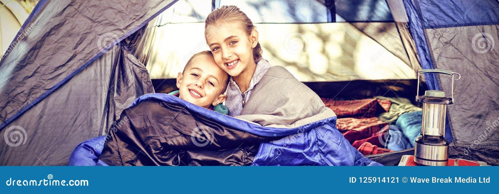 Szczęśliwi rodzeństwa siedzi w namiocie