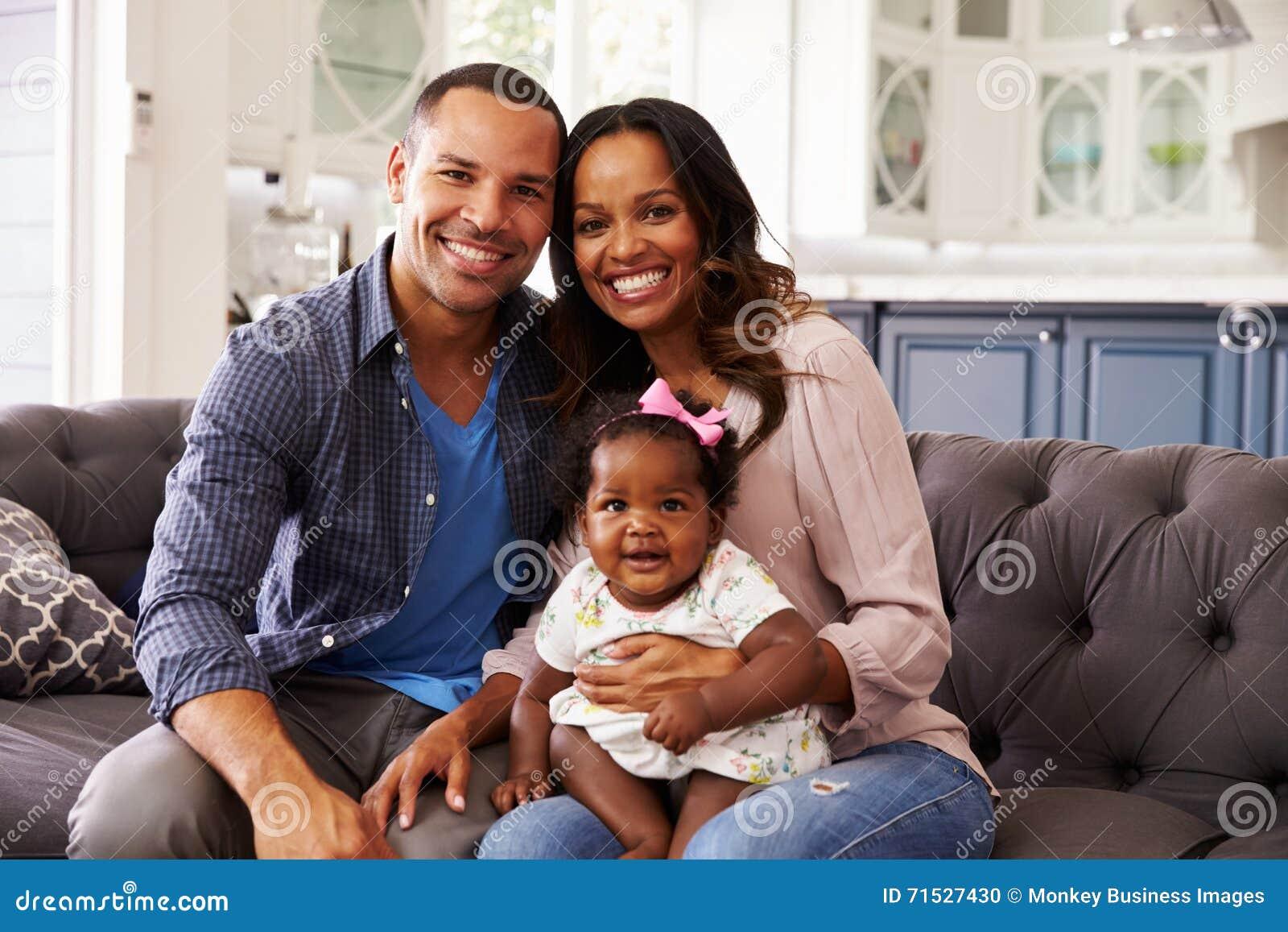 Szczęśliwi rodzice z dziewczynki obsiadaniem na mumï ¿ ½ s kolanie