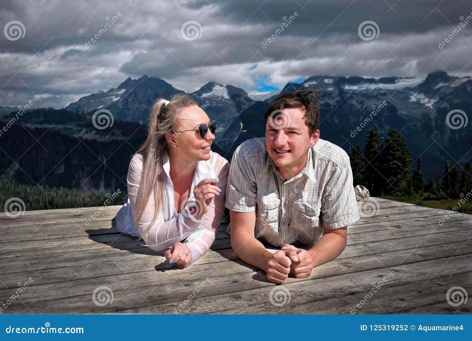 Szczęśliwi uśmiechnięci ludzie obozuje w górach Para małżeńska na namiotowym ochraniaczu ma zabawę i relaksować