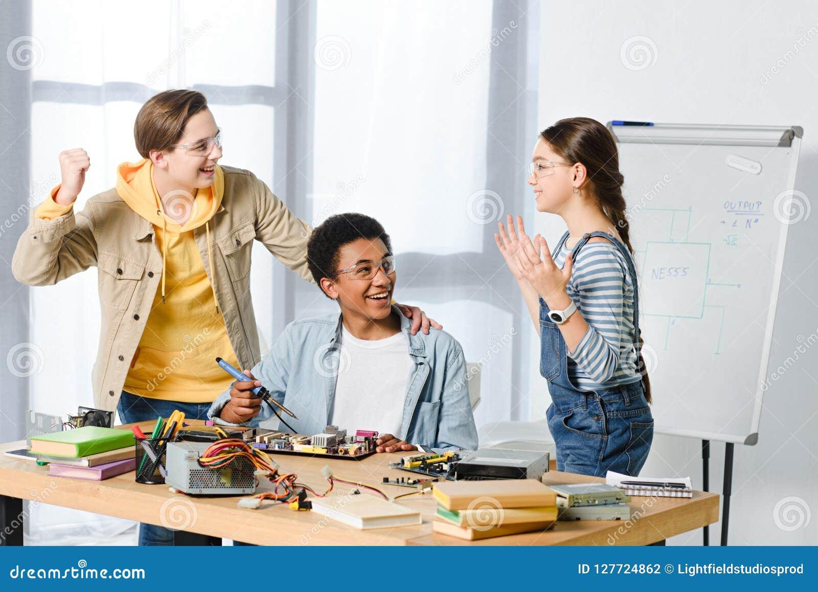Szczęśliwi wielokulturowi nastolatkowie pokazuje tak gest podczas gdy konstruujący