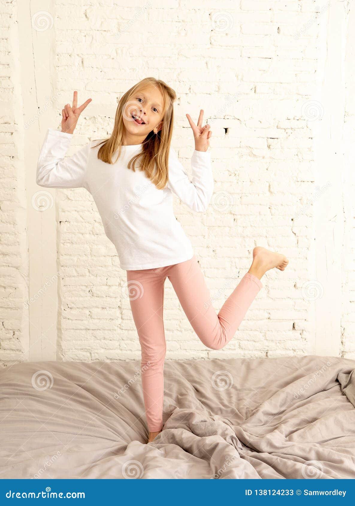 Szczęśliwy śmieszny małej dziewczynki doskakiwanie na łóżku w pozytywnym emocji i dziecka szczęścia pojęciu
