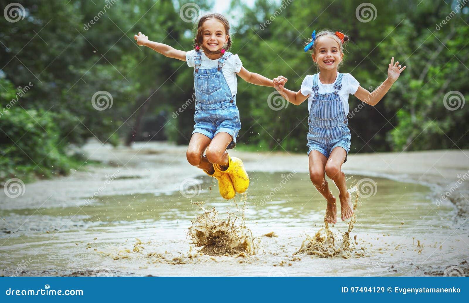 Szczęśliwy śmieszny siostra bliźniaków dziecka dziewczyny doskakiwanie na kałużach w pocieraniu